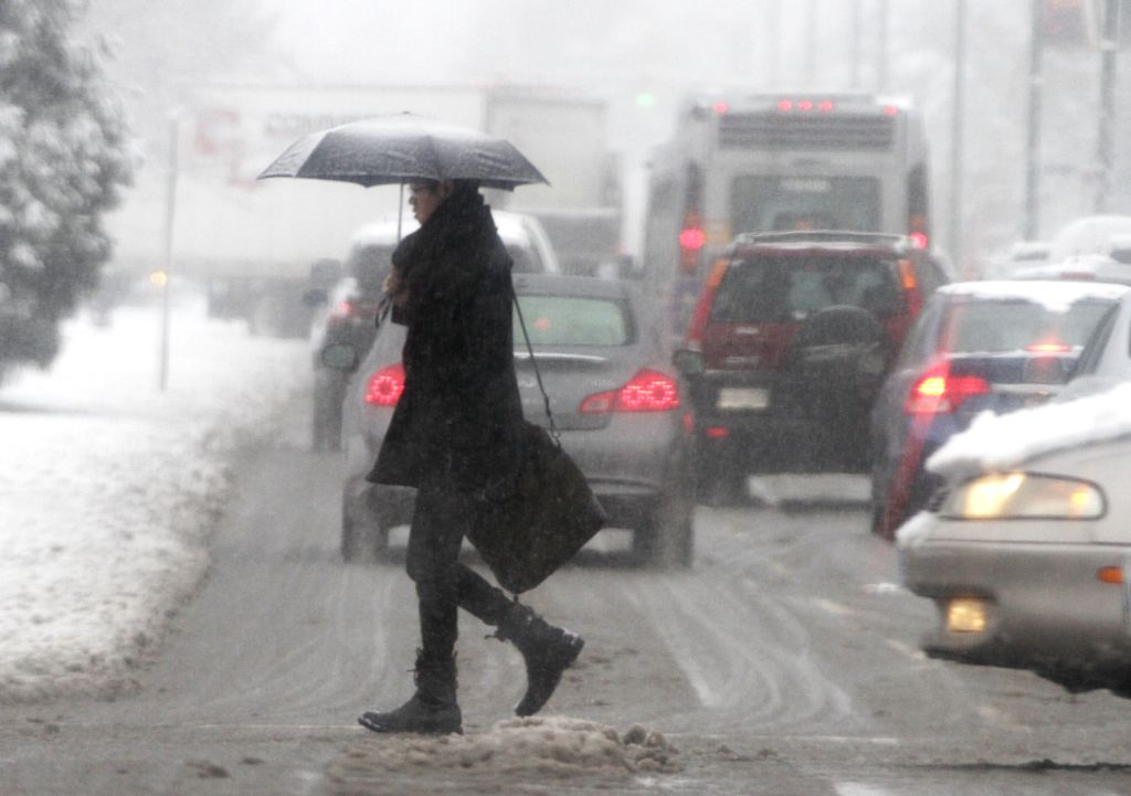 A resident walks on the street with snow in downtown Vancouver, Canada, Dec. 20, 2013. Metro Vancouver was blanketed with snow on Friday. Due to the bad ...