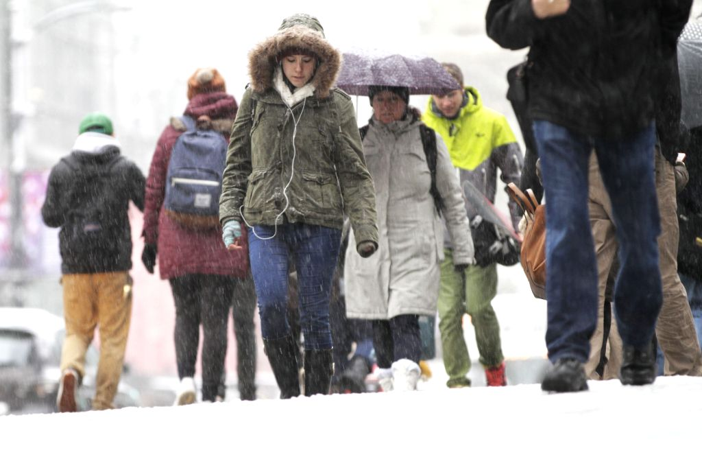 People walk on the street with snow in downtown Vancouver, Canada, Dec. 20, 2013. Metro Vancouver was blanketed with snow on Friday. Due to the bad weather, .