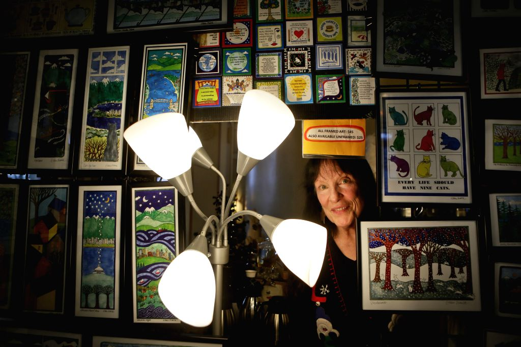 A female artist displays her paintings during the woman artists' winter fair in Vancouver, Canada, Dec. 20, 2014. About 55 female artists from across the province