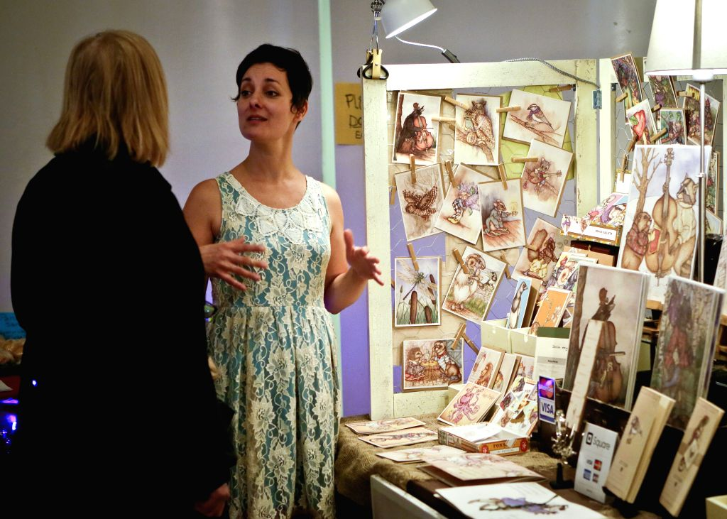 A female artist talks with a visitor about her art works during the woman artists' winter fair in Vancouver, Canada, Dec. 20,  2014. About 55 female artists from .