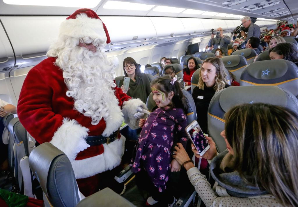 VANCOUVER, Dec. 6, 2018 - A Santa Claus interacts with children inside a plane in Vancouver, Canada, Dec. 5, 2018. About 30 children suffering from illnesses together with their families were invited ...