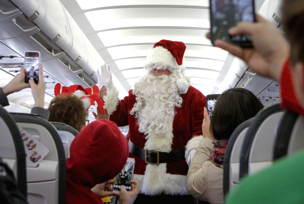 VANCOUVER, Dec. 6, 2018 - A Santa Claus interacts with passengers inside a plane in Vancouver, Canada, Dec. 5, 2018. About 30 children suffering from illnesses together with their families were ...