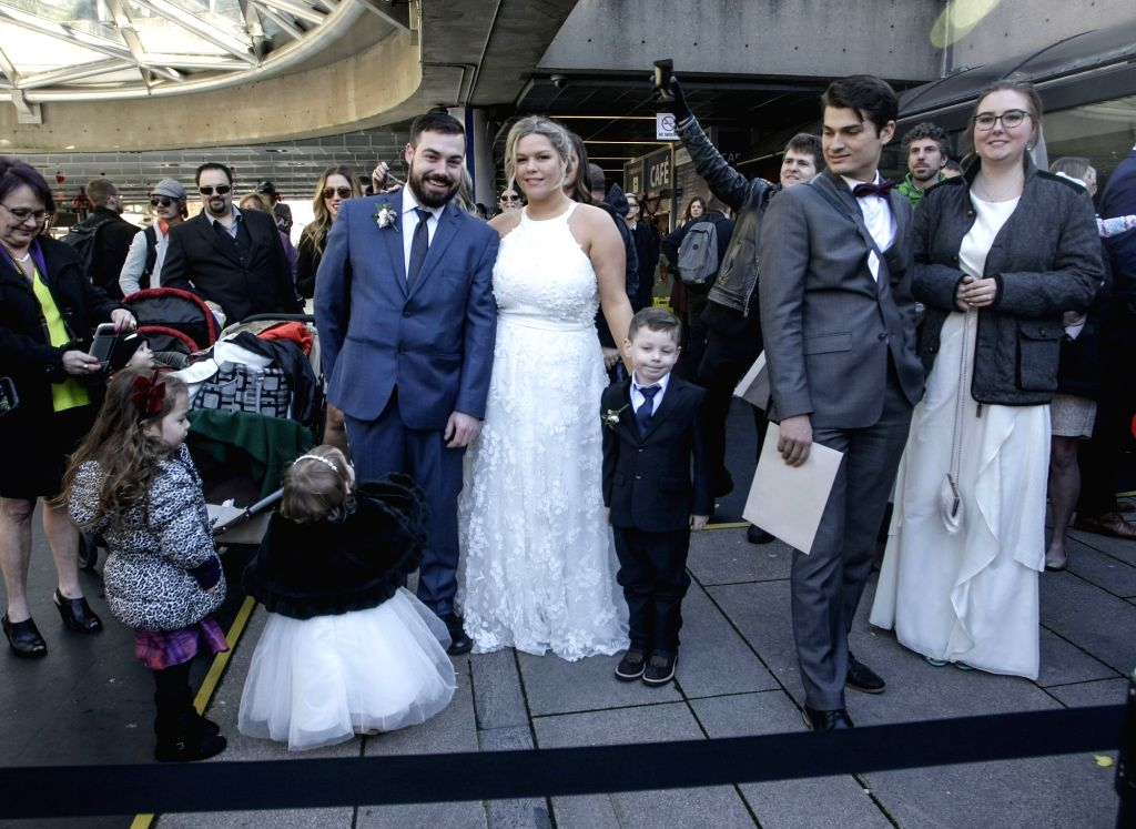 VANCOUVER, Feb. 12, 2018 - Couples take part in a pop-up wedding event at the Robson Square in Vancouver, Canada, Feb. 11, 2018. More than a hundred couples showed up in downtown Vancouver to get ...