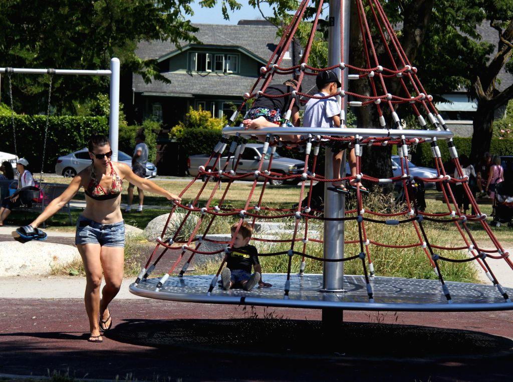 A women plays with her child at the seaside in summer in Vancouver, Canada, July 15, 2014.