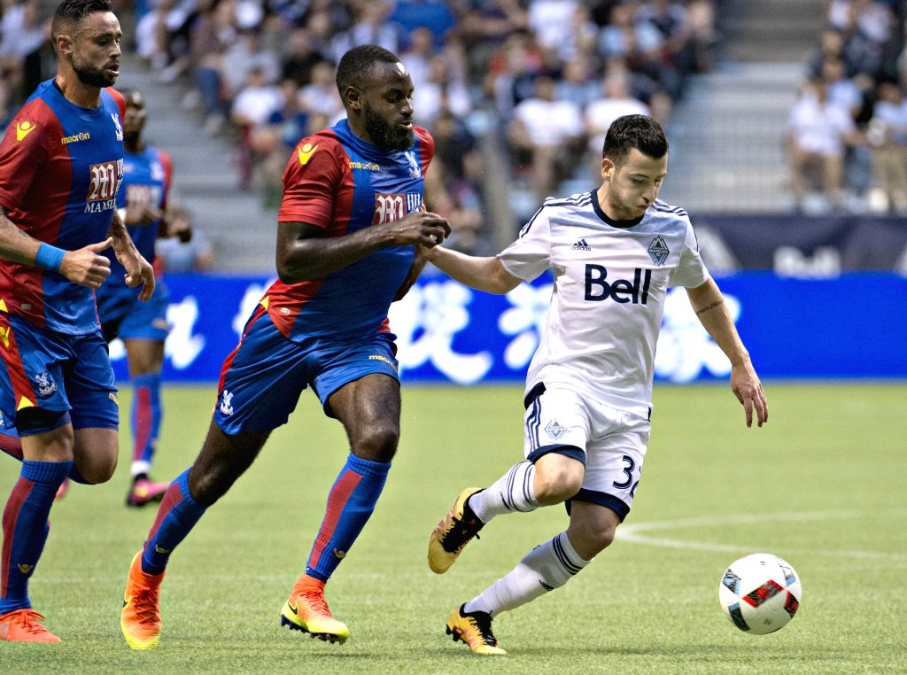 VANCOUVER, July 20, 2016 - Andrew Jacobson (R) of Vancouver Whitecaps vies for the ball with Bakary Sako (C) of Crystal Palace during their international friendly soccer match at BC Place in ...