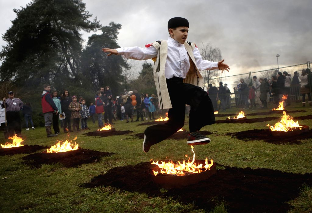 VANCOUVER, March 15, 2017 - A boy leaps over a bonfire with a child during the Persian fire festival in Vancouver, Canada, March 14, 2017. The Iranian community in Vancouver on Tuesday held the ...