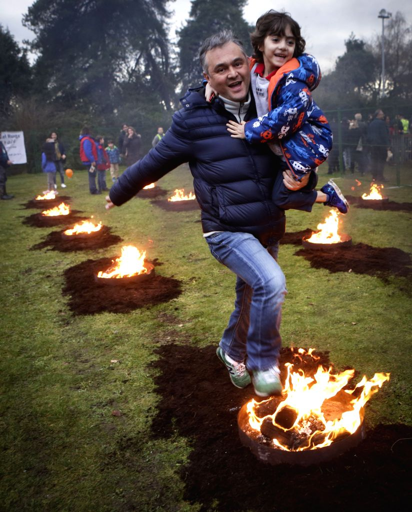 VANCOUVER, March 15, 2017 - A man leaps over a bonfire with a child during the Persian fire festival in Vancouver, Canada, March 14, 2017. The Iranian community in Vancouver on Tuesday held the ...