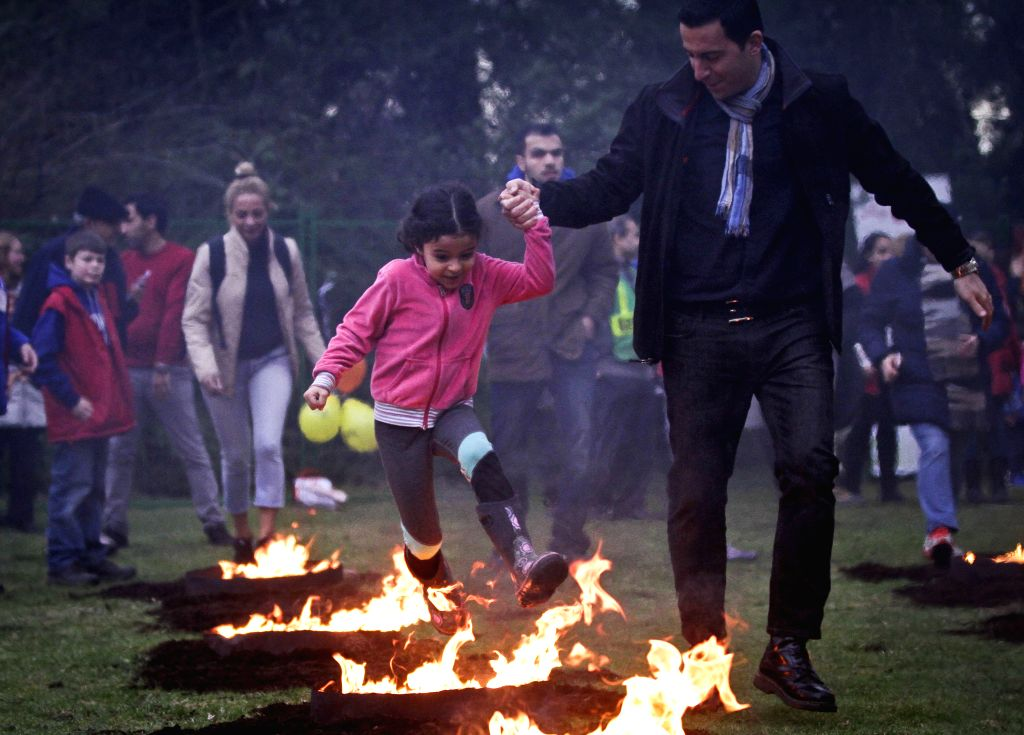 VANCOUVER, March 15, 2017 - People leap over a bonfire with a child during the Persian fire festival in Vancouver, Canada, March 14, 2017. The Iranian community in Vancouver on Tuesday held the ...