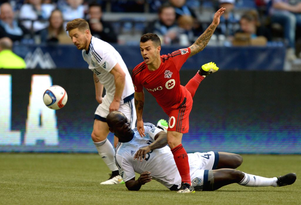 Vancouver Whitecaps' Pa-Madou Kah (bottom) vies with Toronto FC's Sebastian Giovinco during their MLS soccer match at BC Place in Vancouver, Canada, March 7, ...