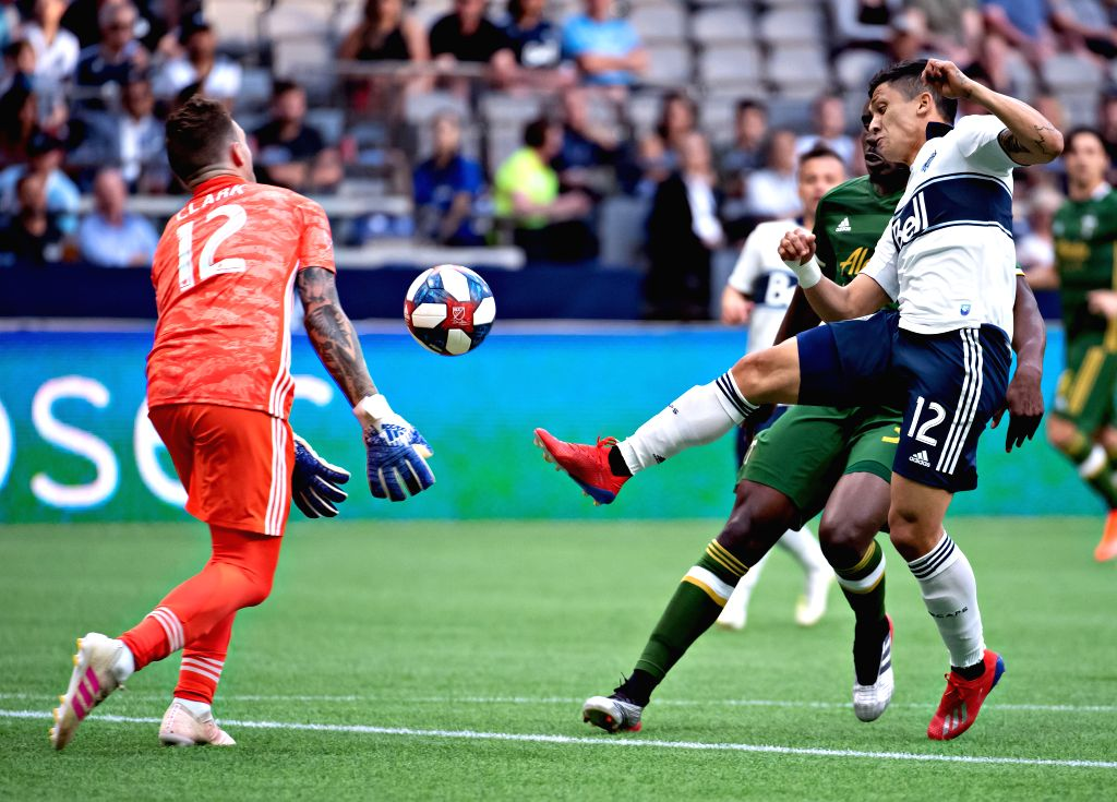 VANCOUVER, May 11, 2019 - Timbers' goalie Steve Clark (L) and Whitecaps' Fredy Montero compete for the ball during a 2019 Major League Soccer (MLS) regular season match between Vancouver Whitecaps ...