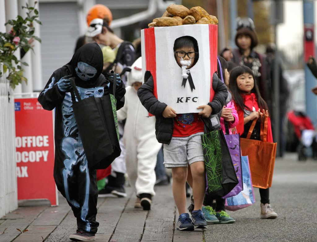 VANCOUVER, Nov. 1, 2018 - Children dressed in costumes go trick-or-treat at the street to celebrate the Halloween in Vancouver, Canada, Oct. 31, 2018.