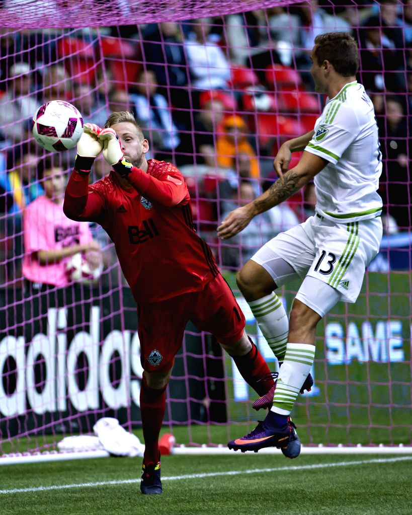 VANCOUVER, Oct. 3, 2016 - Vancouver Whitecaps goalkeeper David Ousted (L) saves a goal from Seattle Sounders FC's Jordan Morris during the Major League Soccer (MLS) in Vancouver, Canada, on Oct. 2, ...