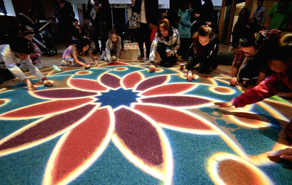 "VANCOUVER, Oct. 30, 2016 - Residents participate in the making of the Indian traditional floor decoration ""Rangoli"" during the Diwali festival event in Vancouver, Canada, Oct. 29, 2016. ..."