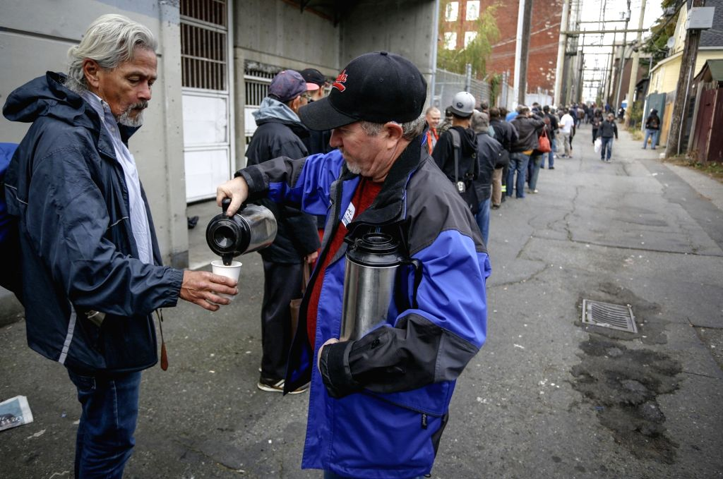 VANCOUVER, Oct. 9, 2017 - A volunteer offers hot drink to the people waiting for free Thanksgiving meals in Vancouver, Canada, on Oct. 9, 2017. The event served more than 3,000 free meals to homeless ...