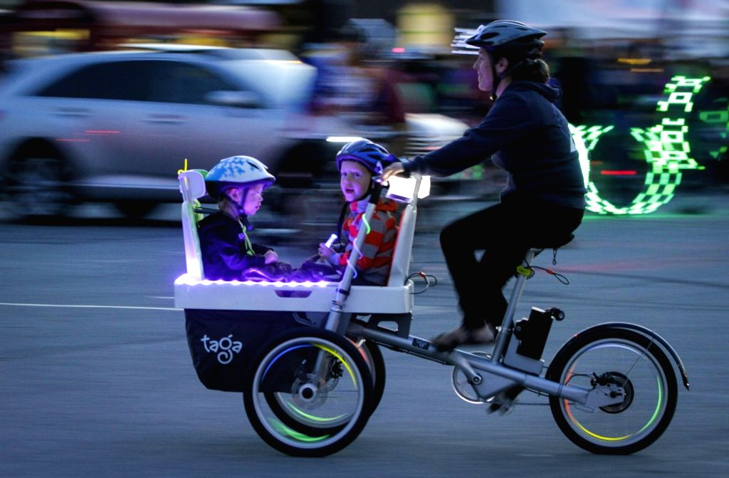 "VANCOUVER, Sept. 17, 2017 - A cyclist rides a bike with her kids during the 2nd annual ""Bike the Night"" event in Vancouver, Canada, Sept. 16, 2017. More than 5,000 people attended the ..."