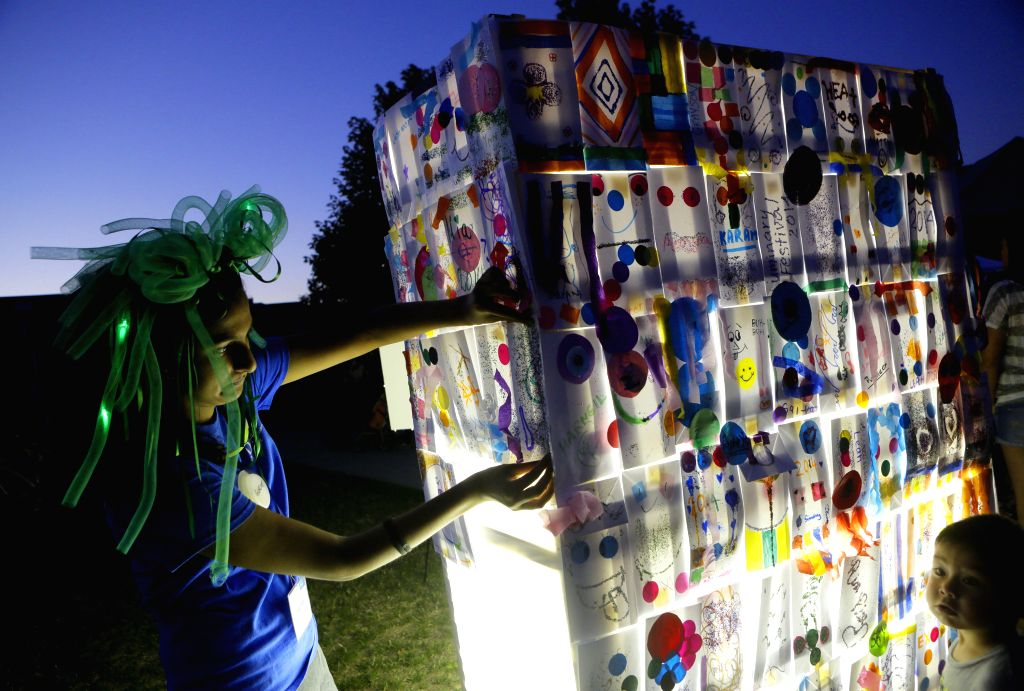 A man decorates a giant lantern at Sunstone Park in Delta, Canada, Sept. 6,  2014. Communities in Delta host a Luminary Festival whereas visitors of different ...