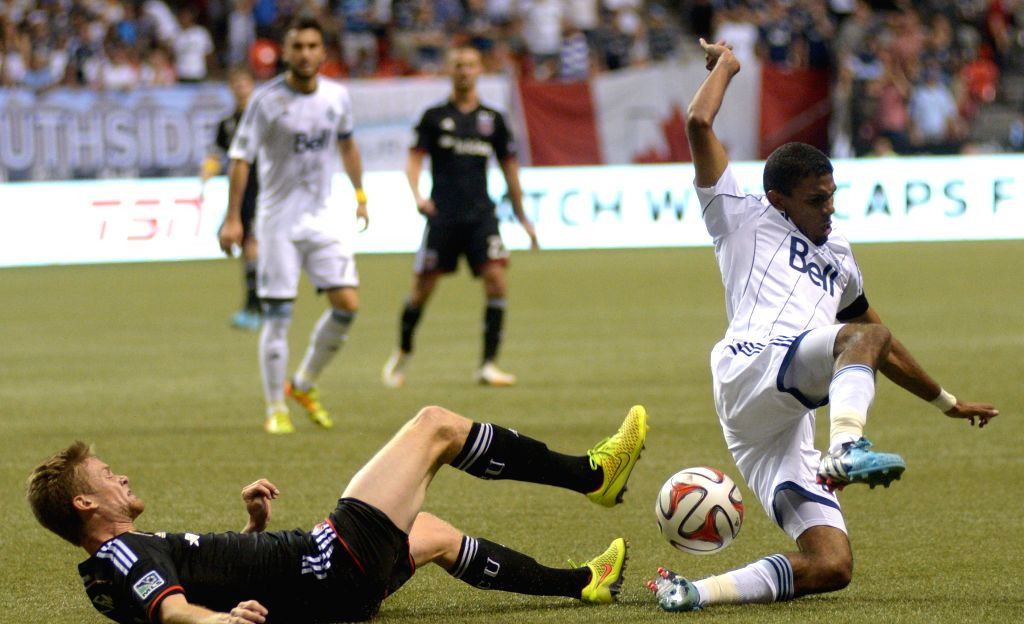 Vancouver Whitecaps' Ethen Sampson (R) battles with DC United' Taylor Kemp during their MLS soccer game at BC Place in Vancouver, Canada, on Sept. 6, 2014. The ...