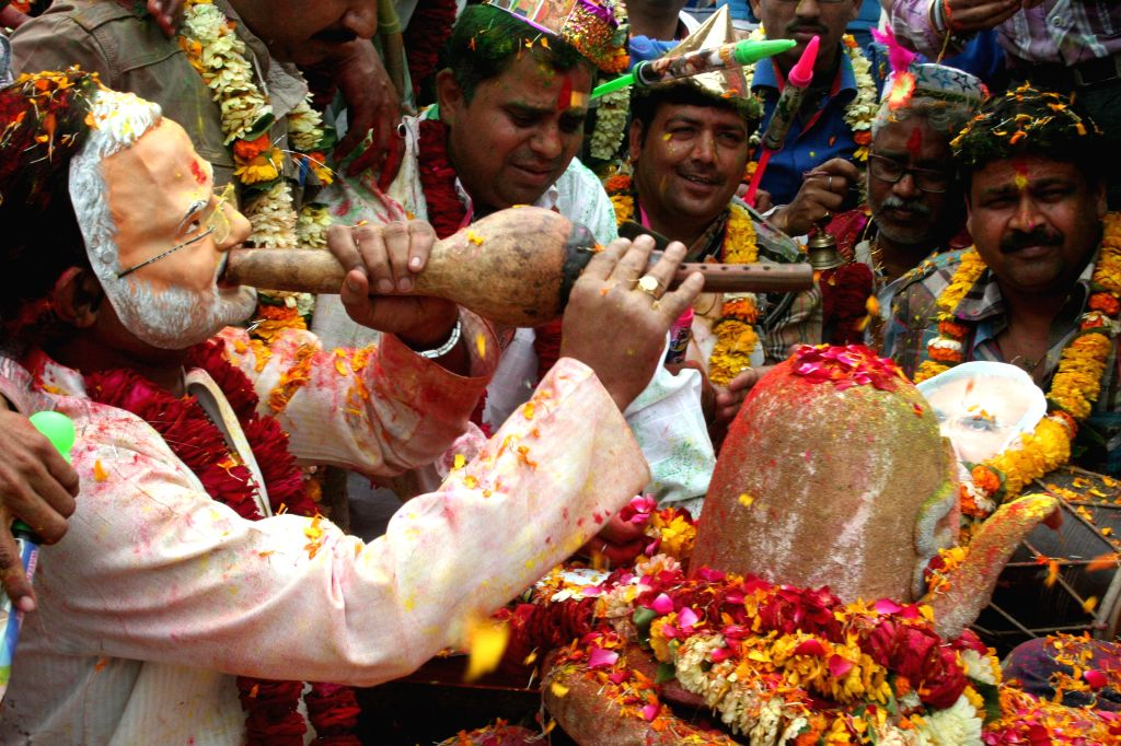 A man wears a Narendra Modi mask as he celebrates Holi at Dashashwamedh Ghat in Varanasi  on March 1, 2015. - Narendra Modi