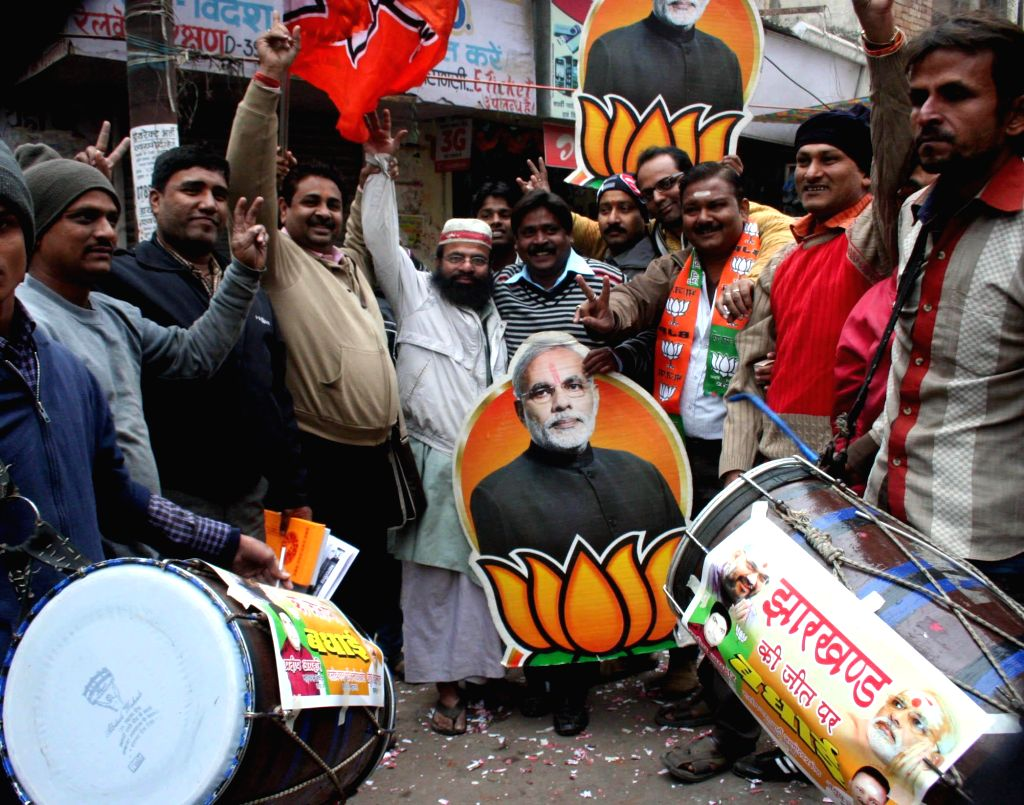 BJP workers celebrate party's performance in Jharkhand and Jammu and Kashmir Assembly polls in Varanasi on Dec 23, 2014.