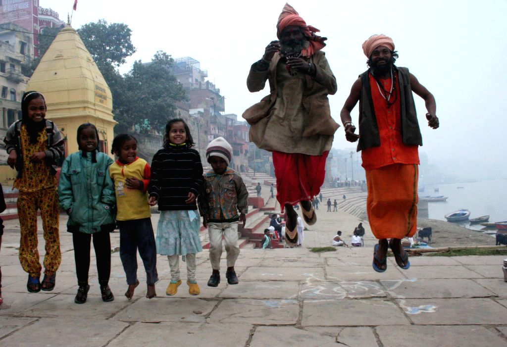 Children and ascetics enjoy themselves on the banks of the Ganga river in Varanasi, on Jan 1, 2015.