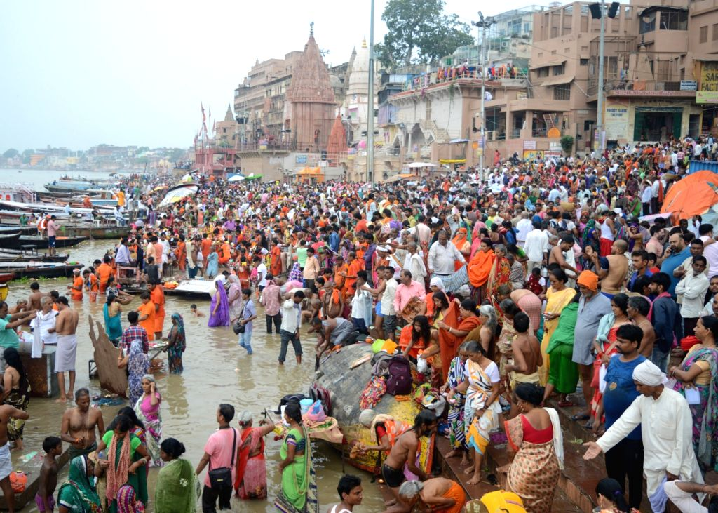 :Varanasi: Devotees take a holy dip in river Ganga on the first day of the Hindu month of Shravan, in Varanasi on July 28, 2018. (Photo: IANS).