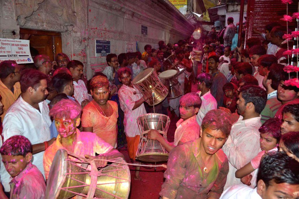 People celebrate Holi at the Kashi Vishwanath Temple on `Rangbhari Ekadashi` in Varanasi, on March 1, 2015.