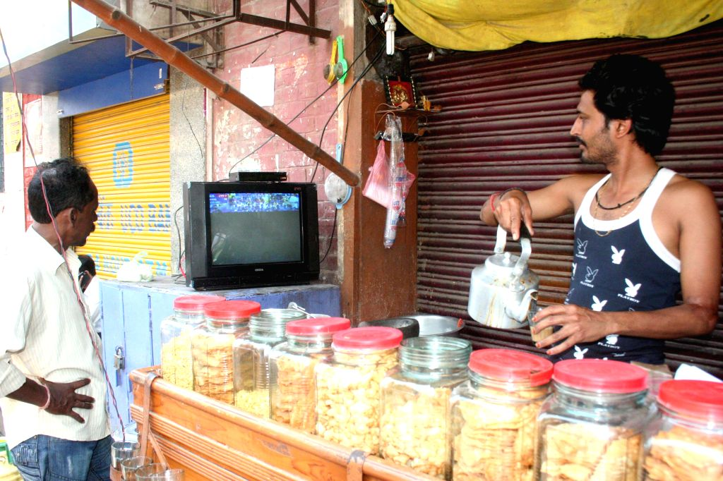 People glued to a television set during the semifinal match of ICC World Cup 2015 between India and Australia in Sydney, at a teat stall in Varanasi  on March 26, 2015.