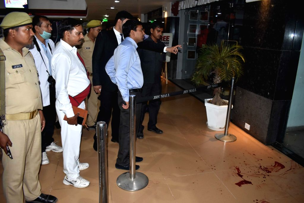 : Varanasi: Police carry out investigations at the site where two persons were killed and two others injured when a man opened fire at them at a mall in Varanasi on Oct 31, 2018. The assailant fled ...