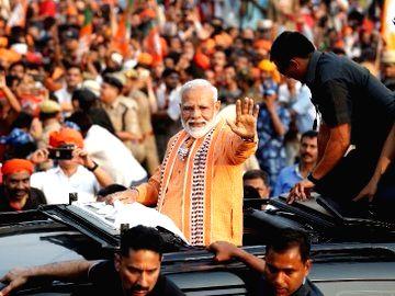 Varanasi: Prime Minister Narendra Modi waves at his supporters during a roadshow ahead of the 2019 Lok Sabha elections, in Varanasi on April 25, 2019. (Photo: IANS) - Narendra Modi