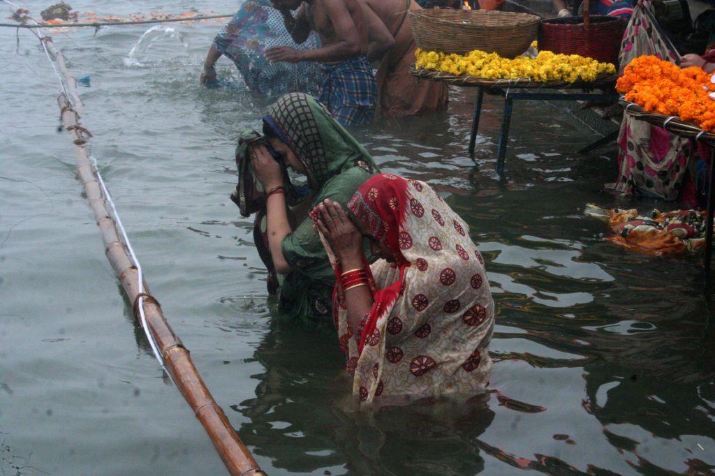 Women take holy dip in the Ganga river on `Makar Sankranti` in Varanasi on Jan 14, 2015.
