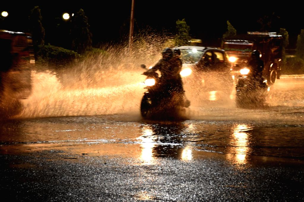 Vehicle run on a water-logged road of Jaipur after heavy rains on July 12, 2018.
