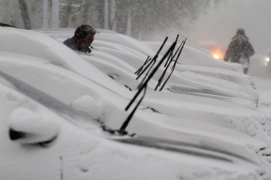 Vehicles are covered with snow in Yantai, a coastal city in east China's Shandong Province, Nov. 26, 2015. A snowstorm hit the city on Thursday.
