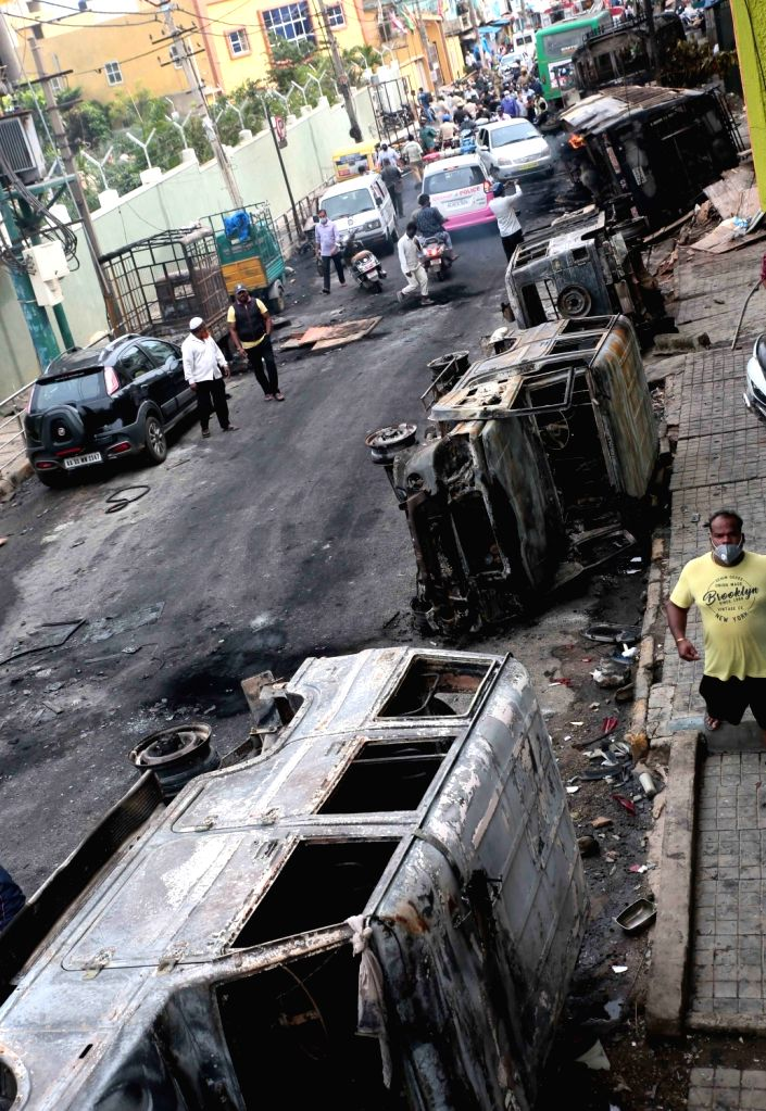 Vehicles burnt by an irate mob during violence that erupted late on Tuesday night that resulted after an inflammatory social media post by Congress legislator Akanda Srinivas Murthy's ... - B.