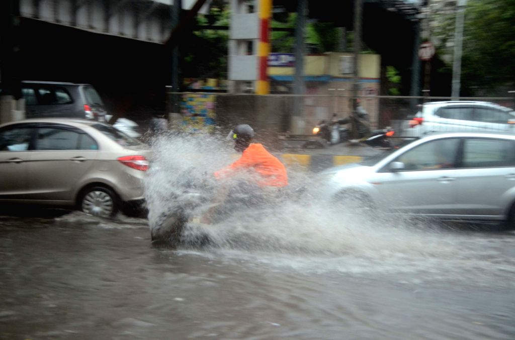 Vehicles drive through a water-logged street after heavy rains in Mumbai, on July 3, 2018.