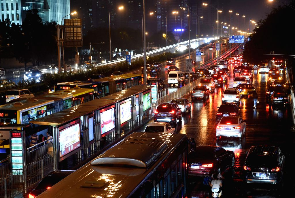Vehicles move at a rainy night in Beijing, China, July 27, 2015. As heavy rain hit Beijing on Monday, local weather station issued a yellow signal warning for ...