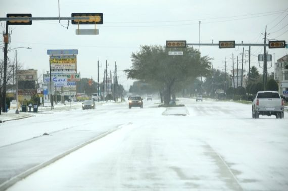 Vehicles move on a snow-capped road in Houston, Texas, the United States, on Feb. 15, 2021.