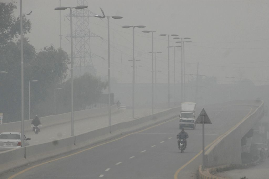 Vehicles move on the road in heavy fog in northwest Pakistan's Peshawar, Nov. 25, 2015.