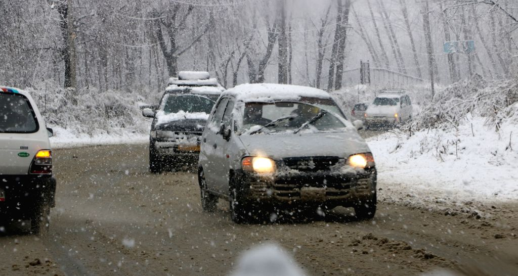 Vehicles move through the snow-covered streets during snowfall in Srinagar on Feb 12, 2018. Moderate to heavy snowfall started in the valley as rain lashed the plains on Monday breaking the ...