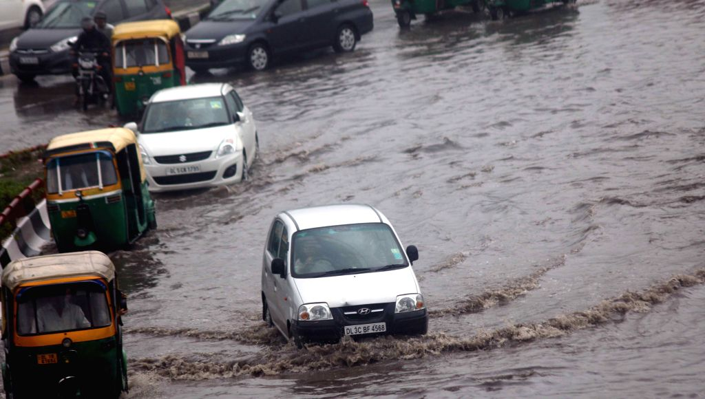 Vehicles ply on a submerged road as heavy rains in New Delhi on July 11, 2015.
