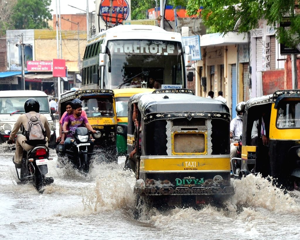 Vehicles ply on water logged roads of Bikaner after rains on June 28, 2016.
