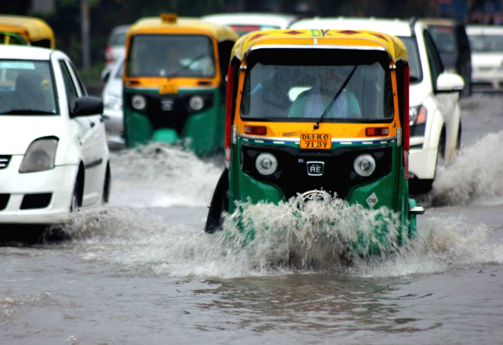 Vehicles ply on water logged roads of New Delhi, on Aug 11, 2015.
