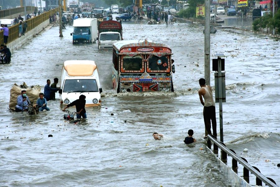Vehicles run through floodwater in the southern Pakistani port city of Karachi, on Aug. 26, 2020.