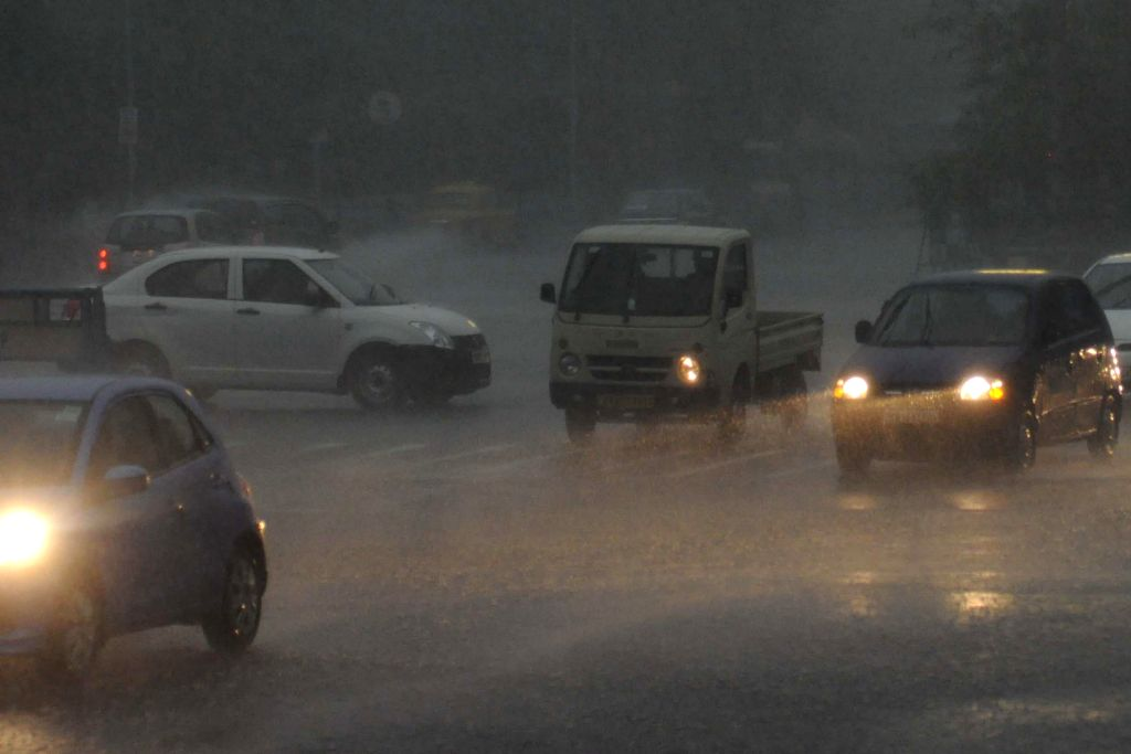 Vehicles run with their headlights turned on during heavy rains in Kolkata on June 25, 2014.