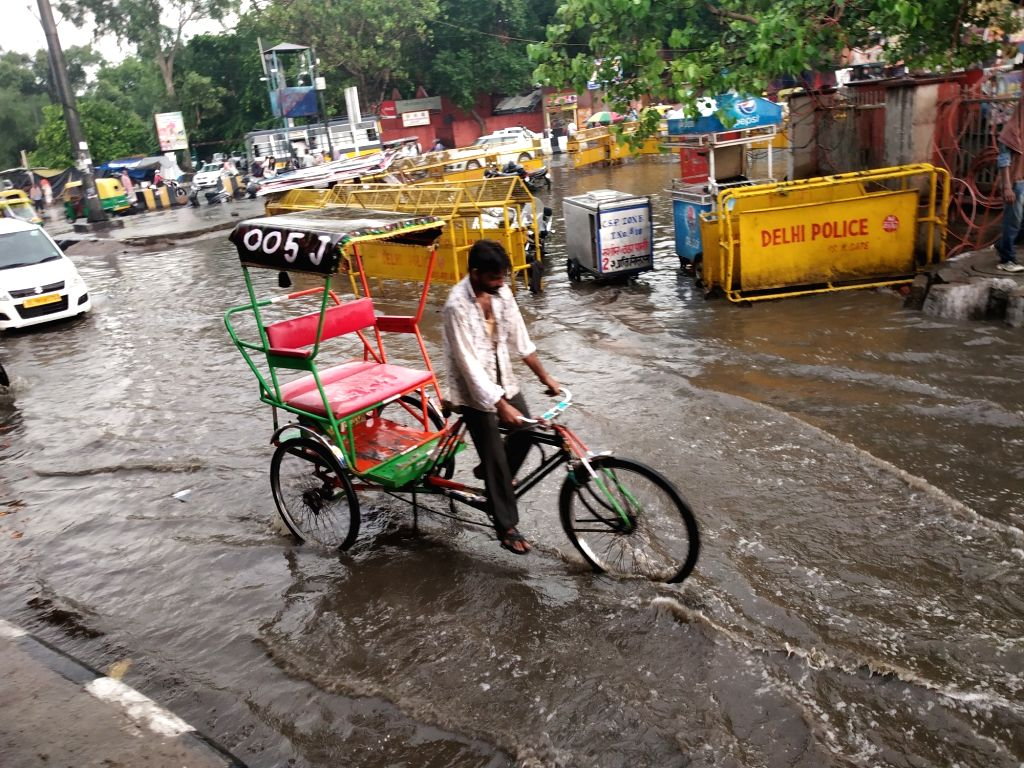 Vehicles struggle through a water logged streets in New Delhi, on July 21, 2019.