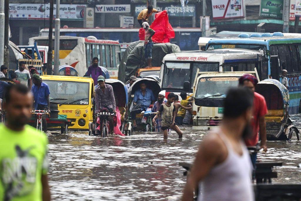 Vehicles struggle through a waterlogged street after heavy rains lashed Dhaka, in Bangladesh on July 23, 2018.