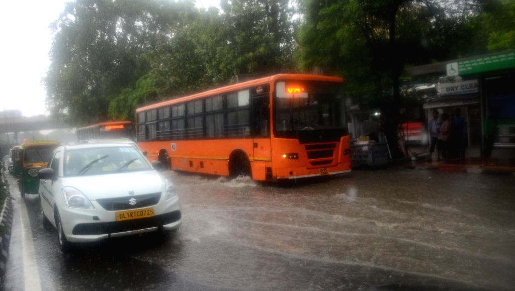 Vehicles struggle through a waterlogged streets in New Delhi, after heavy rains lashed the national capital on July 13, 2018.