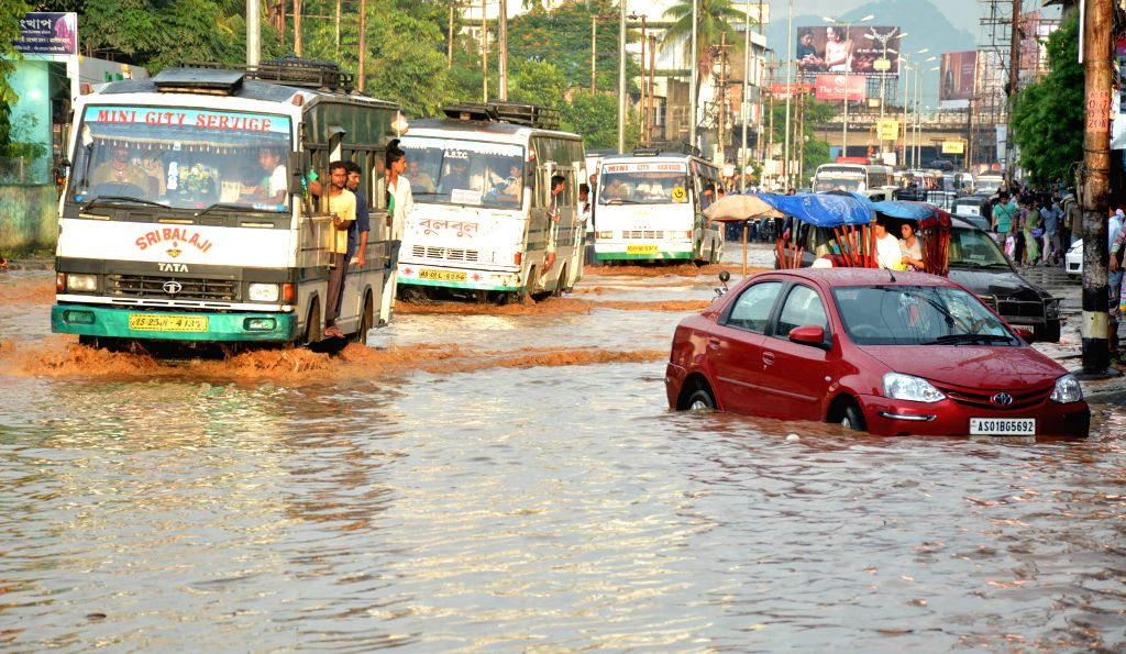 Vehicles struggle through flooded streets of Guwahati on Sept 8, 2014.
