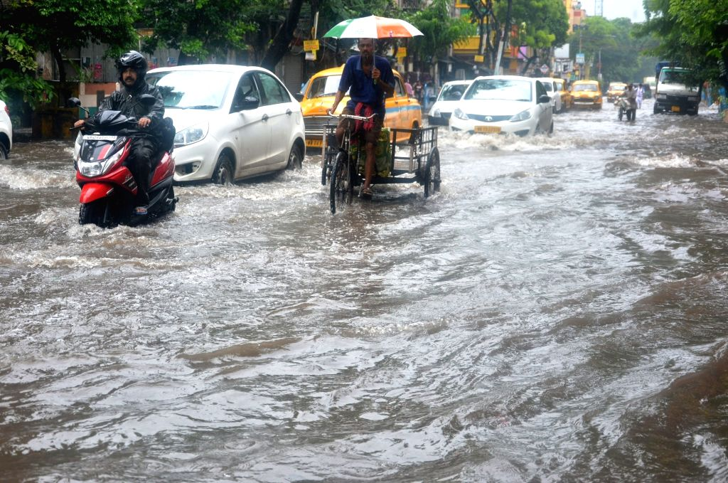 Vehicles struggle through the waterlogged streets, in Kolkata on July 26, 2018.