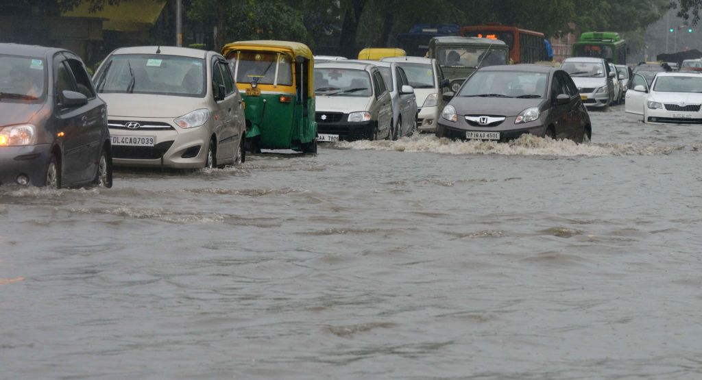 Vehicles struggle through waterlogged roads of New Delhi as heavy rains lashed national capital on Sept 11, 2014.