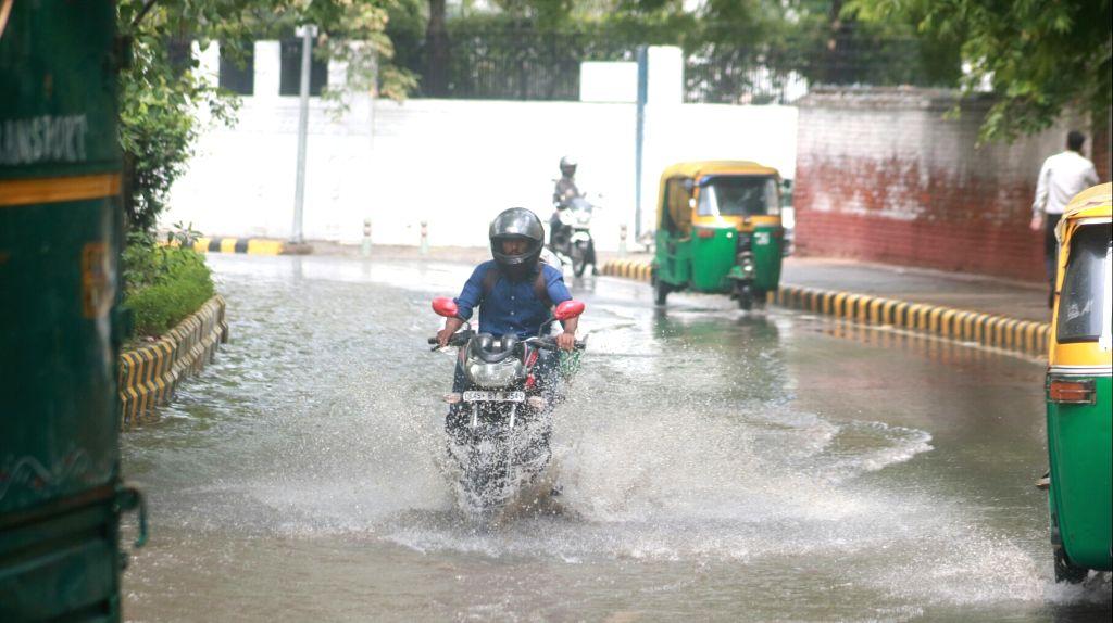 Vehicles struggle through waterlogged roads of New Delhi on June 21, 2017.
